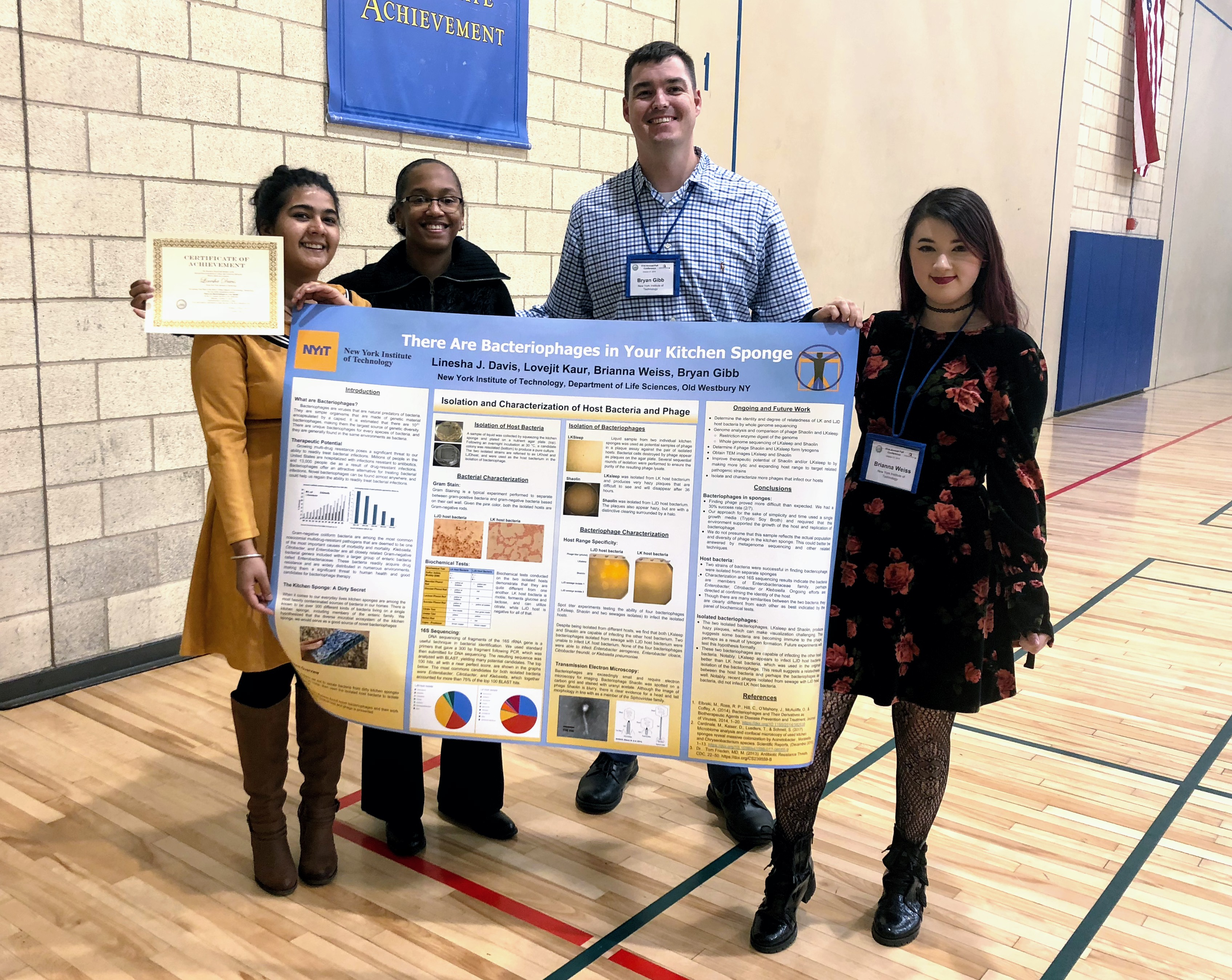 Life Science students, Lovejit Kaur, Linesha Davis and Brianna Weiss with mentor Bryan Gibb, which took first place for their work on bacteriophages in kitchen sponges.