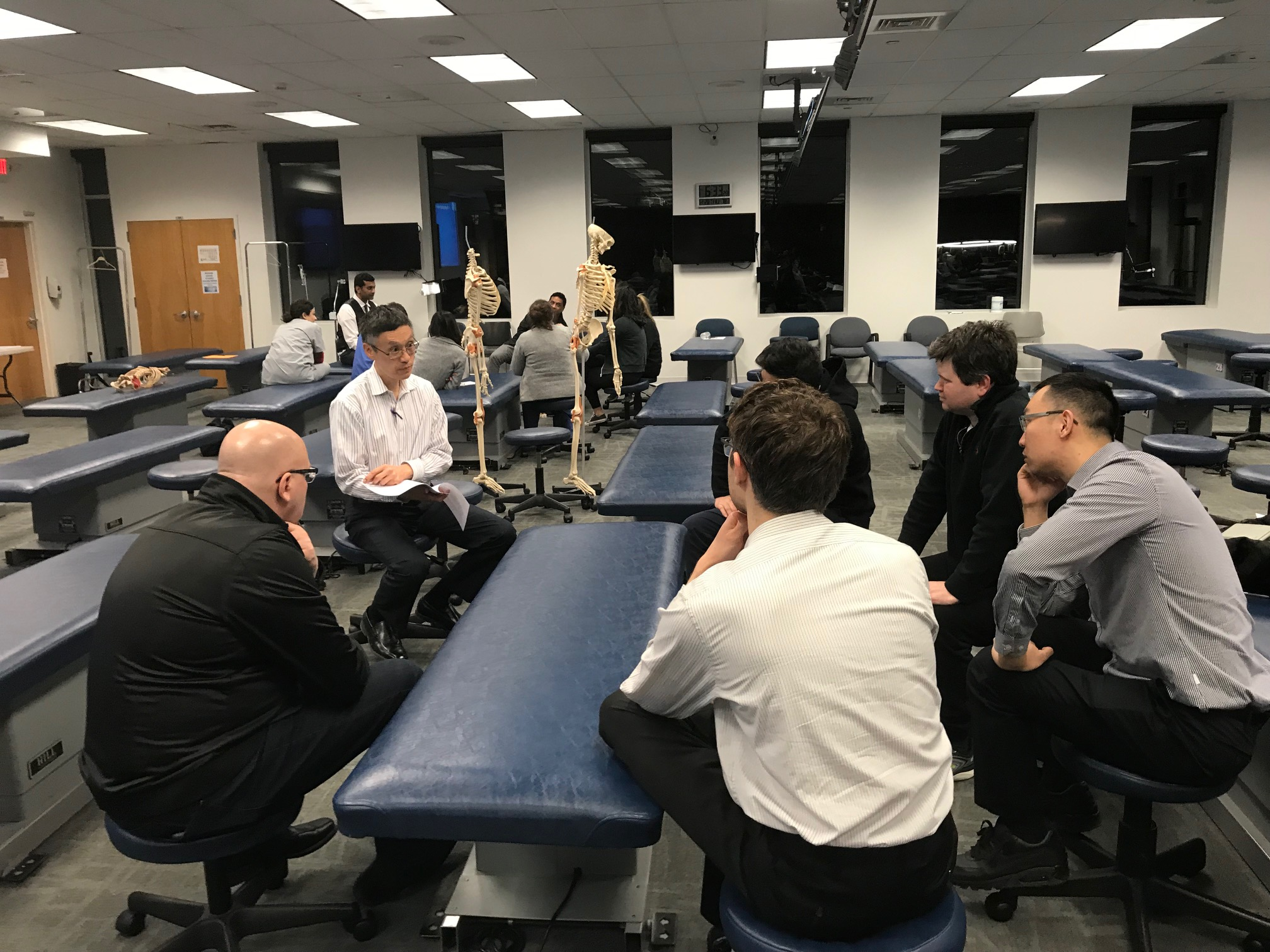 Dr. To Shan Li D.O. and the physician participants reviewing case scenarios with osteopathic considerations