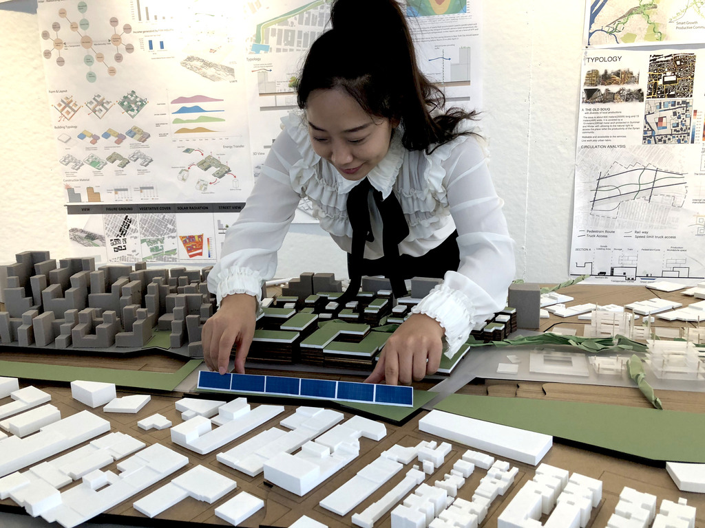 Graduate Student Wenshuo Liu placing solar panels on her model